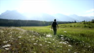 Young man walks across mountain meadow towards sunrise video