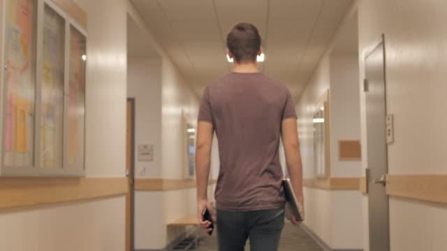 Young Man Walks College Halls video