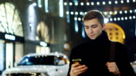 A young man walks down the street and reads sms video