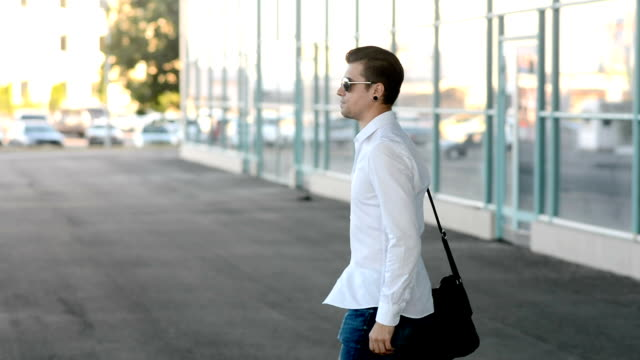 A young man walks, serious and looks around, waiting for someone video