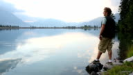 Young man walks to shoreline of mountain lake video