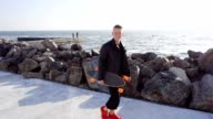 young man walks with his longboard by the sea video