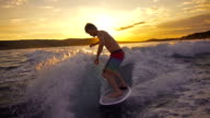Surfing Behind Boat At Sunset Super Slow Motion video