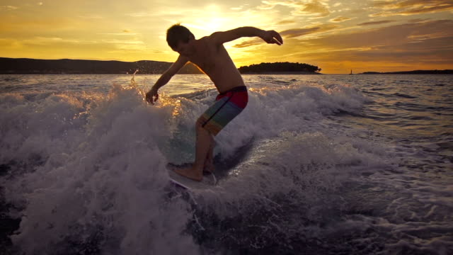 Young man wave surfing behind a boat at sunset video