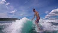 Young man wave surfing behind a boat video