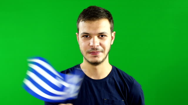 Young man waving the Greece Flag on Green Screen background video