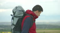Young man wearing camping outfit and rucksack looking at mountains video