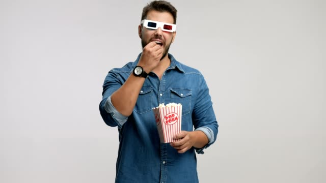 Young man wearing pair of 3D glasses and laughing video