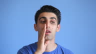 Young Man Whispering Gossip On Blue Background video