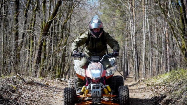 A young man who rides a sports quad bike lifts the front wheels upwards by making a small jump, a person quickly rides a hill in the autumn forest video