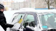 Young man with a mustache in a winter jacket cleans a car from the snow. video