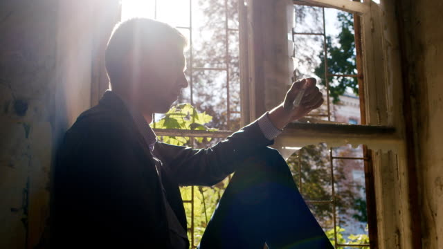 Young man with a syringe in his hand. Sitting in an abandoned house in the sun. Risk of addiction video