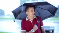 A young man with an umbrella smiling. video