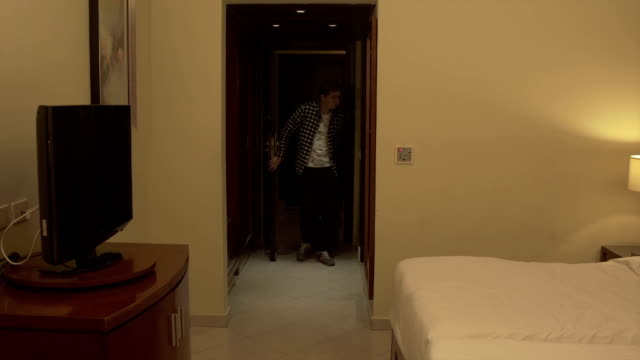Young man with baggage Check in hotel room video
