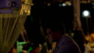 Young man with cell in outdoor cafe at night video
