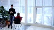 Young man with glasses and a black pullover, talking to a classmate on background of panoramic windows at university video