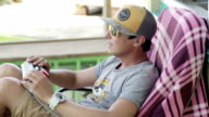 young man with glasses and a cap with a remote controller video