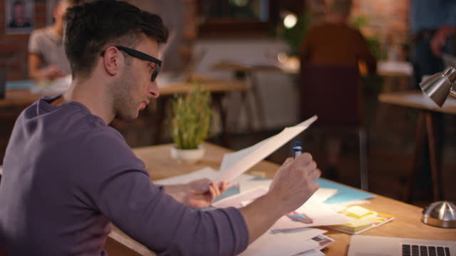 Young man with glasses writing behind his office desk video