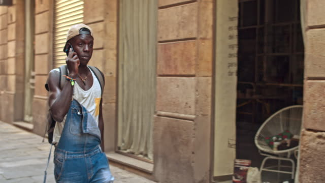 Young man with mobile phone walking in the city video