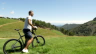 Young man with mountain-bike looking mountain panorama in outdoor nature scenery during summer day - gimbal steadicam HD video footage video