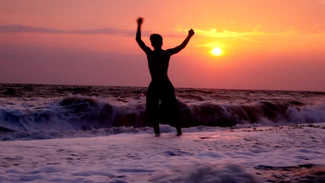 Young man with raised hands, sunset sea in background video