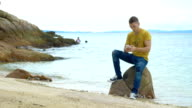 Young man with smartphone sitting on rock at beach video