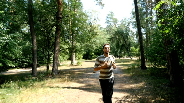 A young man with sportive figure in black pants runs in a forest in slow motion video