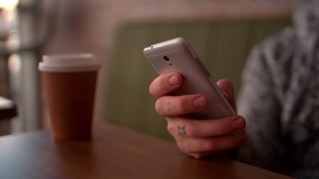 Young man with tattoos texting on smartphone video