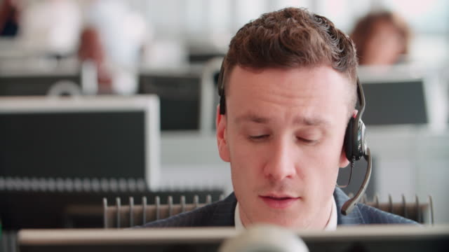 Young man working in a call centre using a headset video