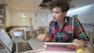 Young man working on digital tablet and laptop. video