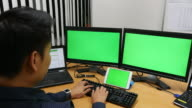 Young man Working with multi green screen video