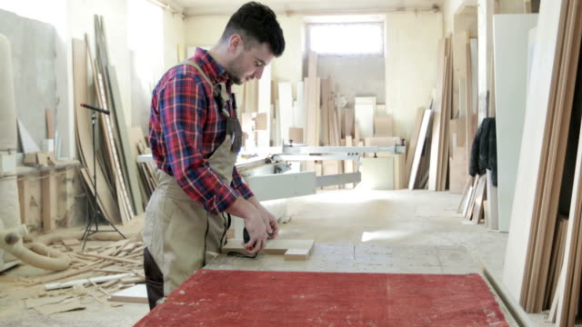 4K A young man works on furniture production. Carpenter or joiner worker`s hands using roulette, measuring something on wooden plank. video