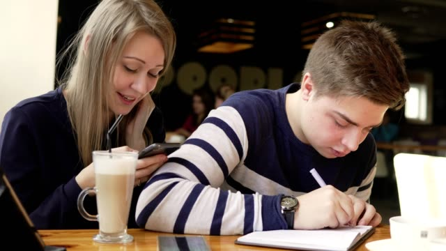 Young man writing a letter or doing his homework in a cafe. His girlfriend sitting behind and using her smartphone. Cup with coffe at the table. Shot in 4k video