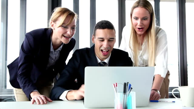 Young manager and two businesswoman with laptop, high-fiving and cheering video