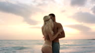 Young man-woman couple in love hugs and kisses at ocean beach sea-side at sunrise or sunset in summer - gimbal steadicam HD video footage video