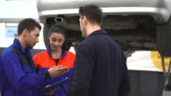 Young mechanics and custumer looking car in auto repair shop video