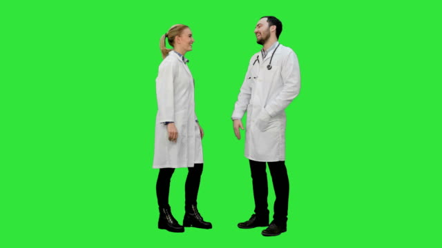 Young medical students give each other five after exam on a Green Screen, Chroma Key video