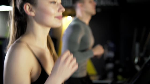 Young men and women are engaged on a treadmill in the gym video