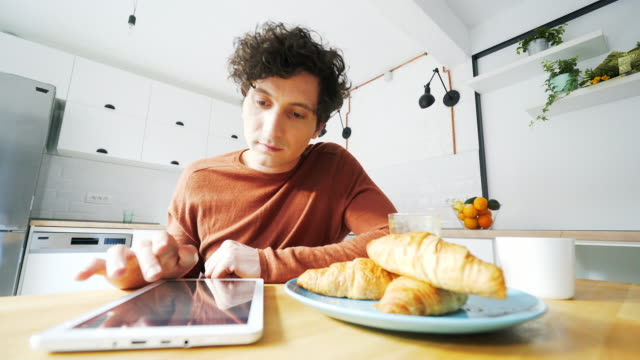 Young men taking breakfast while using a digital tablet. video