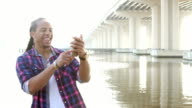 Young mixed race man on waterfront using mobile phone video