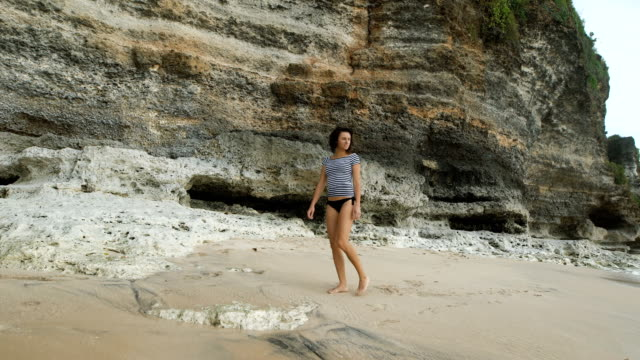 Young model n black swimsuit and striped shirt is walking on the sand along the Balinese bay and looking at the sea. Beautiful fashion brunette posing on the beach against a background of big rock video