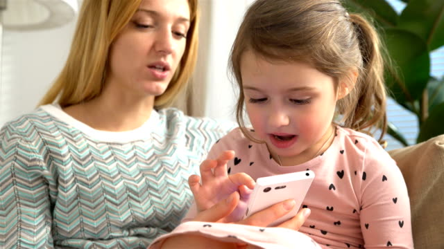 Young mom and her daughter are playing a smartphone and smiling while sitting on sofa at home video