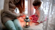 Young mother and her adorable daughter lit Christmas lantern on a window sill. Dolly shot. video