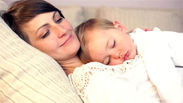Young mother and her baby, sleeping in bed video