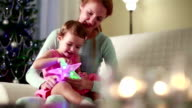 Young mother and her cute daughter playing with Christmas stars.Slow motion. video