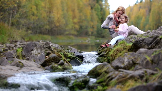 A young mother and her cute daughter sitting near the forest stream and play with water. video