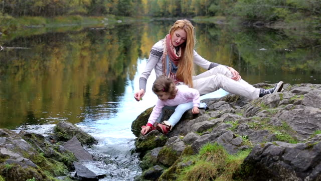 A young mother and her cute daughter sitting on the Bank of a forest lake and playing with water. video