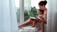 Young mother and her little daughter with laptop on the window-sill video