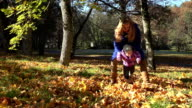 Young mother and her toddler girl have fun in autumn nature. FullHD video