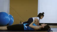 Young mother exercising with baby in gymnasium video